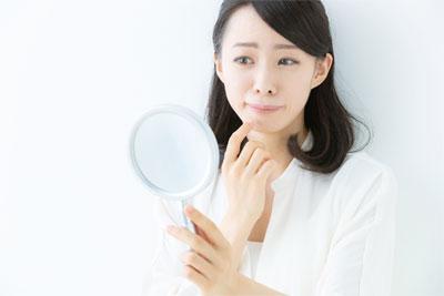 鏡を見て悩む女性